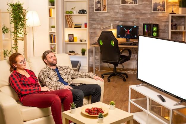 밤 늦게 거실에서 흰색으로 분리된 tv 화면을 보고 있는 커플.