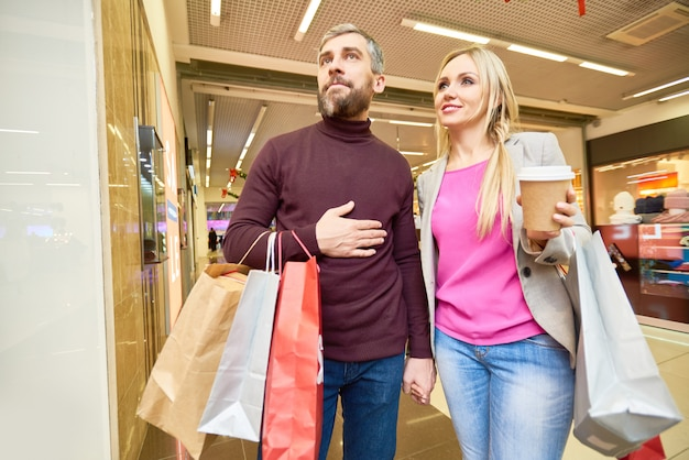 Пара смотрит на витрины в торговом центре