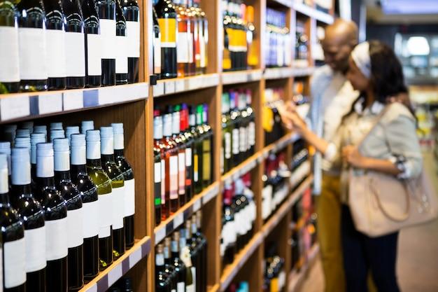 食料品のセクションでワインのボトルを探しているカップル