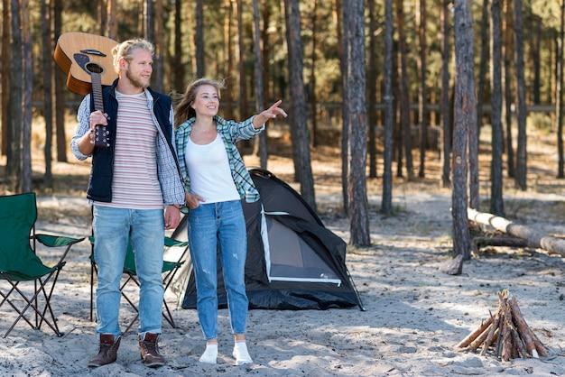 Пара смотрит в сторону и стоит рядом со своей палаткой