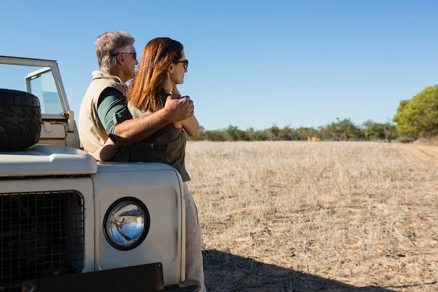 Couple looking away while standing by off road vehicle on field