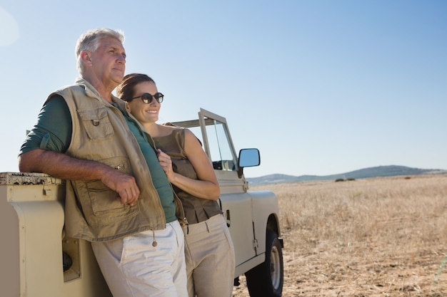 Couple looking away while standing by vehicle on field