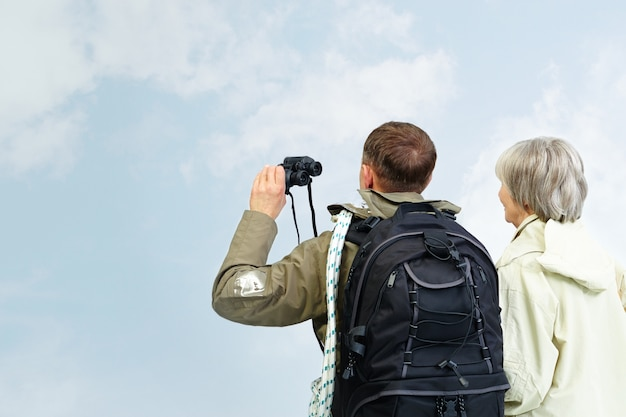 Couple looking at the blue sky with binoculars