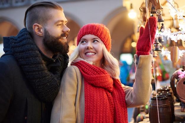 Coppia in cerca di ornamenti natalizi di notte