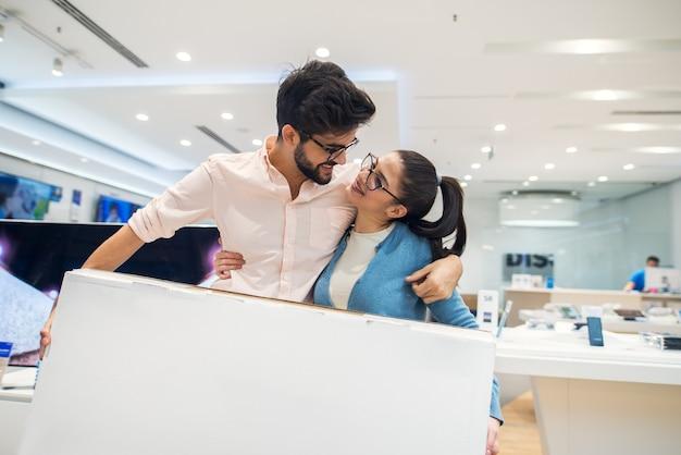Пара смотрит друг на друга и держит коробку новых умных гаджетов после покупки в техническом магазине.