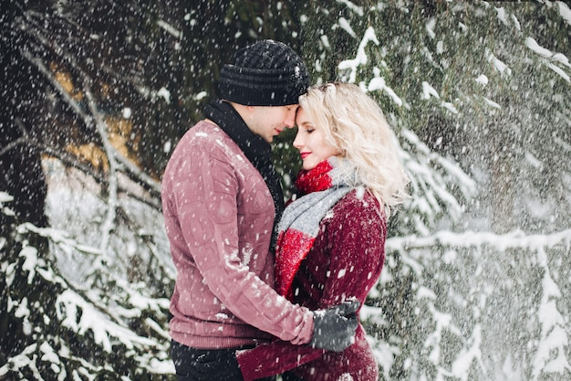 Couple looking each other in snowing forest.