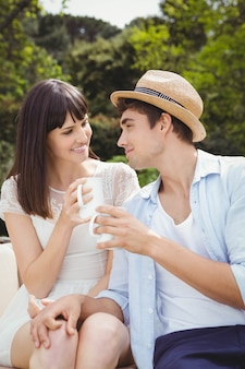 Couple looking at each other while having coffee outdoors