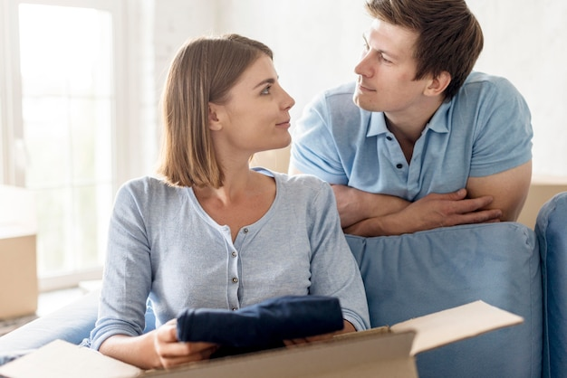 Couple looking at each other while packing box to move house