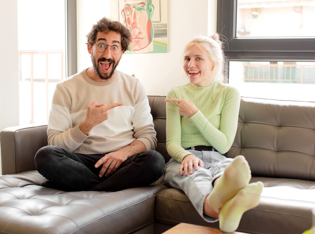 Couple looking excited and surprised pointing to the side and upwards to copy space