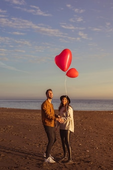 Couple looking at flying heart balloon on sea shore