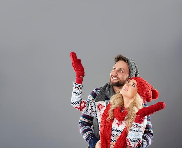 雪が降っている様子を見ているカップル