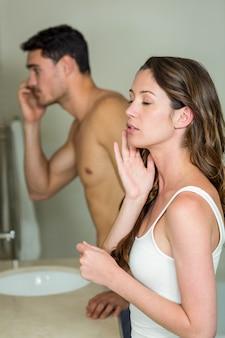 午前中にバスルームの鏡で見ているカップル