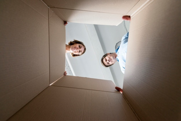 Пара смотрит в пустую коробку во время упаковки для переезда