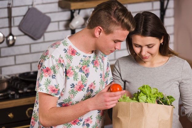Couple looking inside paper bag with groceries