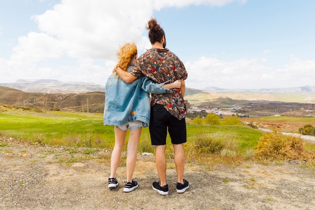 Couple looking into distance from hilltop
