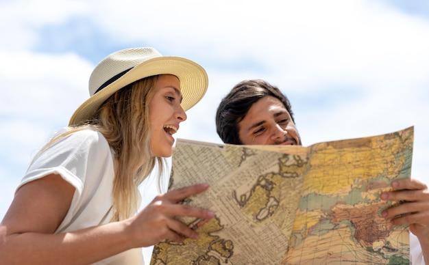 Couple looking at map medium shot