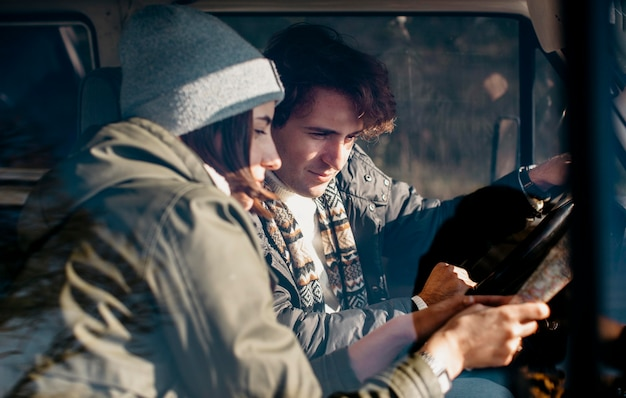 Couple looking at a map while road tripping
