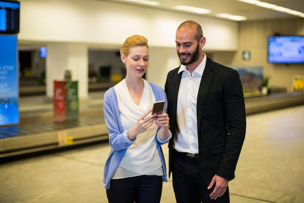 Couple looking at mobile phone in waiting area