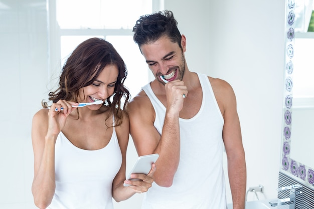 Couple looking in mobile phone while brushing teeth