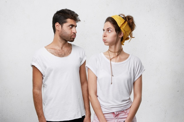 Couple looking offensive at each other blowing their cheeks having argue. trendy man with fashionable hairstyle looking with insult at his wife