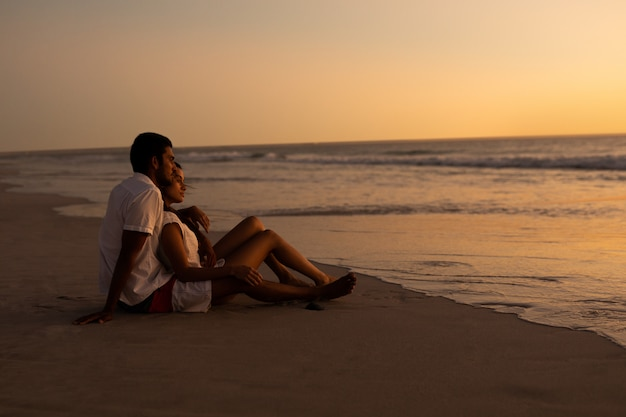 Couple looking at sea on the beach during sunset