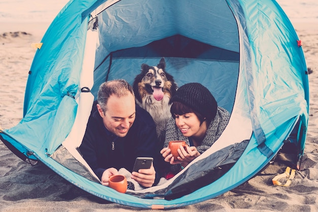 Couple looking at the smart phone and have fun inside a tent in free camping on the beach dog border collie behind them looking at the camera. vintage colors and vacation family concept. alternative t