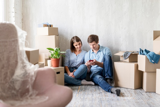 Couple looking at smartphone while packing to move house