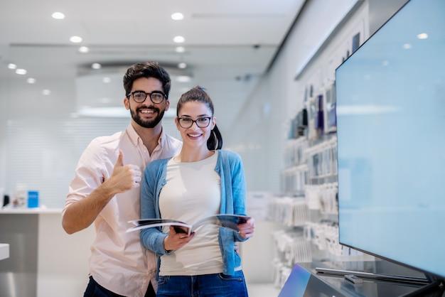 Соедините смотреть ehilr камеры st стоя в техническом магазине. человек, давая пальцы вверх и женщина, держащая каталог.