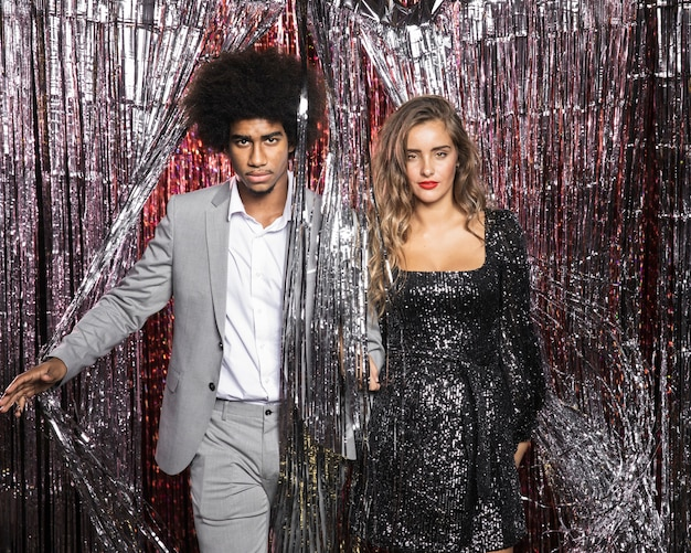 Couple looking straight from curtain of sparkles
