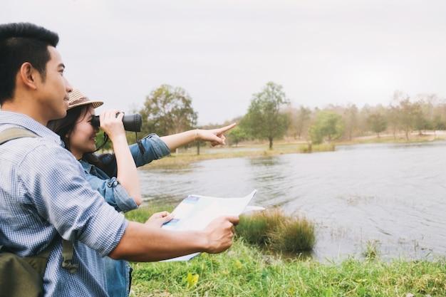 Couple looking through binoculars finding new mountain way