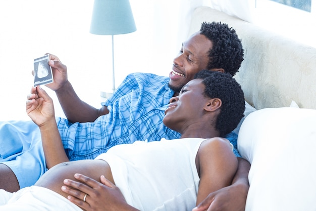 Couple looking at ultrasound scan while relaxing
