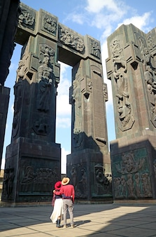 Couple looking up to the pillars of the chronicle of georgia, a stunning monument located near tbilisi, georgia