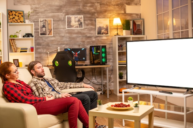 Couple looking at white isolated tv screen late at night in living room.
