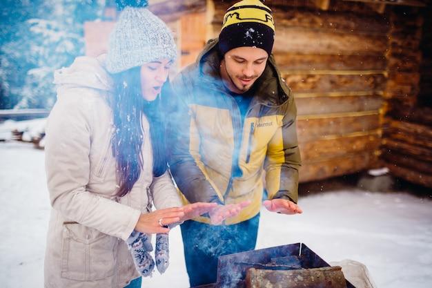 カップルは冬の森で彼らの手を暖かく幸せに見える