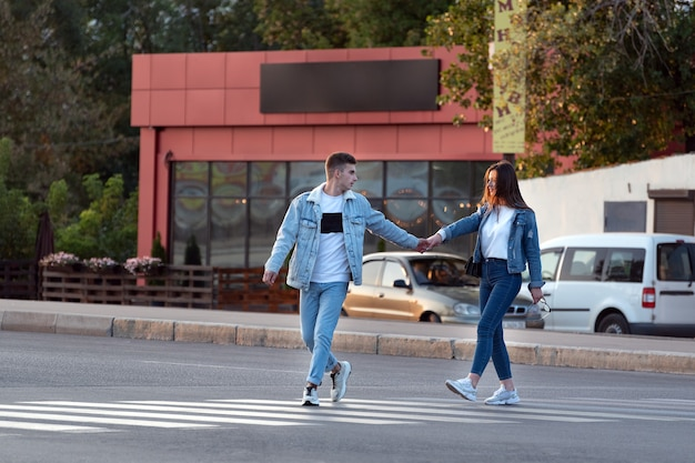 Couple in love across road at pedestrian crossing. always together.