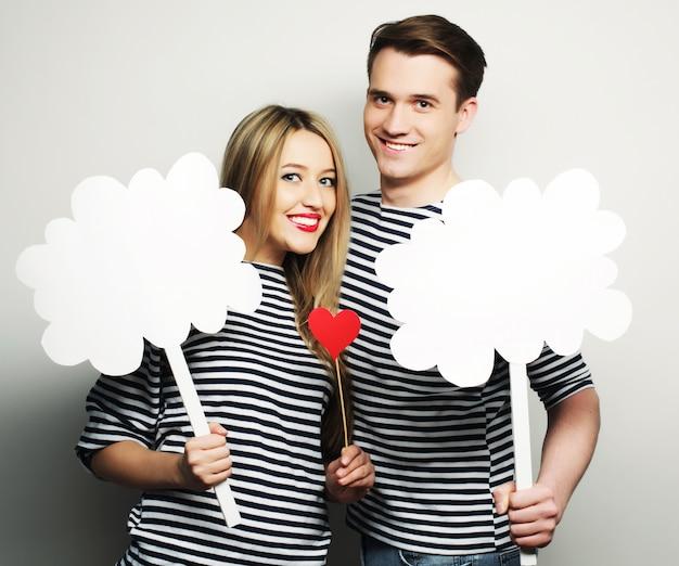 カップル、愛、家族の概念:スティックに空白の紙を保持している好色なカップル。