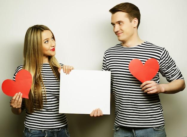 カップル、愛、家族のコンセプト:白い空白と赤いハートを持った幸せなカップル。