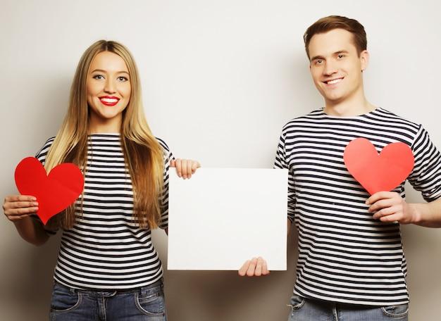 カップル、愛、家族の概念:白い空白と赤いハートを保持している幸せなカップル。