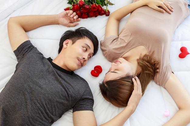 カップル、愛とバレンタインデーのコンセプト。お互いの顔を見て、赤い婚約金のリングボックスと寝室の白い毛布でベッドに横たわっている2人の笑顔のアジア人の男性と女性の肖像画