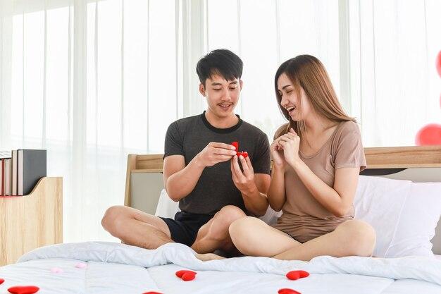 カップル、愛とバレンタインデーのコンセプト。ミニ赤いハート型の枕、寝室の風船と寝室のベッドに座っている金の指輪を持つ2人の笑顔のアジア人男性サプライズ女性の肖像画。