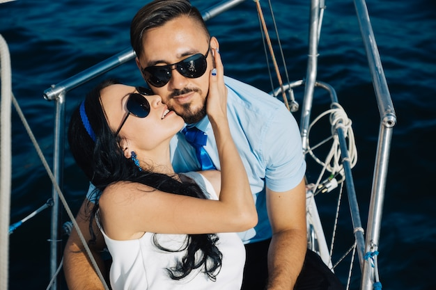 Couple in love are sitting on the deck of the yacht, embracing each other.