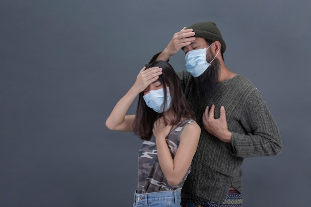 Couple love are wearing mask while headache on gray black wall.