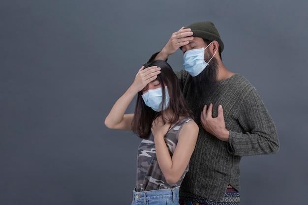 カップルの愛は灰色の黒い壁に頭痛をしながらマスクを着ています。