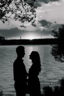 Couple in love back light silhouette at lake orange sunset, romantic.