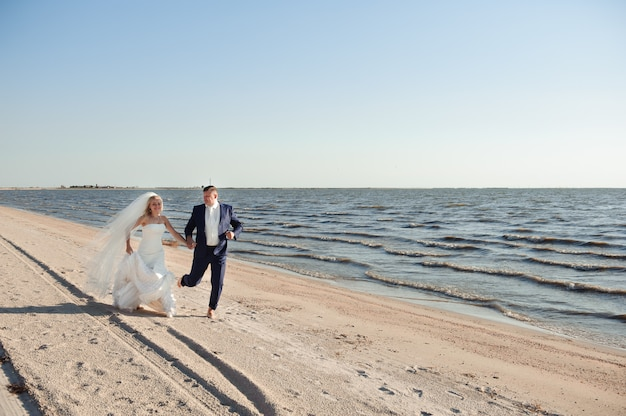 Couple in love on the beach on their wedding day.