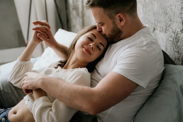 Couple in love in the bedroom. slender brunette. stylish interior.