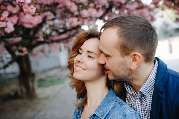 Couple in love in a blooming apple orchard lying on the blanket