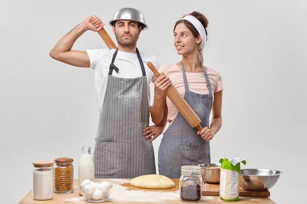 Coppia innamorata impegnata nella cucina familiare, sicura di sé in cucina, prepara l'impasto per preparare la torta, ha tutti gli ingredienti necessari, tiene il mattarello, si prepara per la festa cibo, cucina, concetto di ricetta