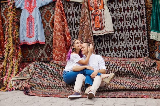 Couple in love buys a carpet and handmade textiles at an oriental market in turkey. hugs and cheerful happy faces of men and women