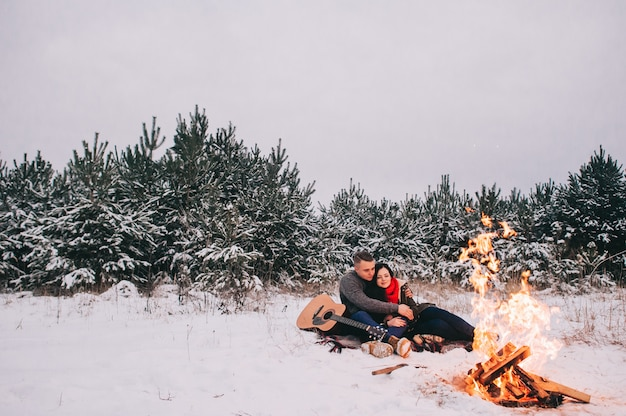 Couple in love by a campfire. winter